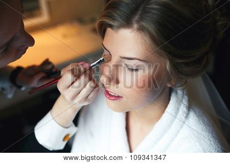 Applying make up to bride