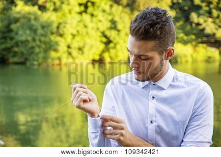 Contemplative young man sitting beside river
