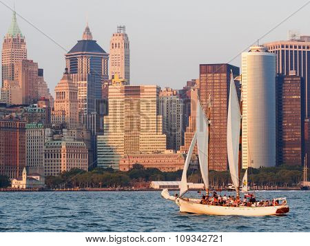 NEW YORK,USA - AUGUST 17,2015 :  Lower Manhattan at sunset with a sailboat on the bay