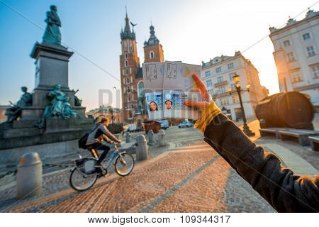Female hands holding Ukrainian passports with Shengen visas on the Krakow city center background