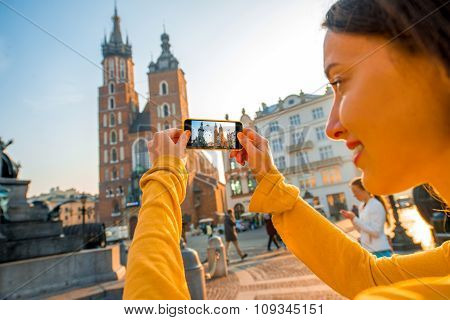 Female traveler photographing with mobile phone in Krakow
