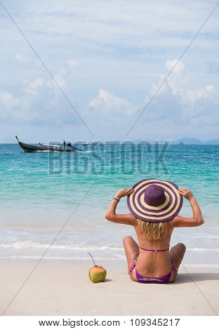 Happy young woman in straw hat with  on the beach
