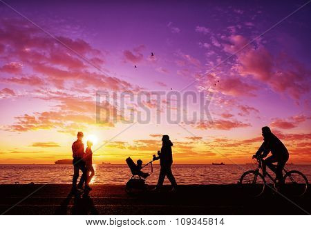 Silhouettes of people enjoying a walk by the seaside of the town during sunset