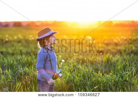 Little boy with a camera in the field