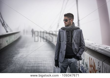 Handsome trendy man walking on a bridge in winter