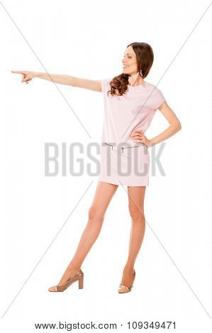 Young slim pretty woman in pink dress point finger with outstretched arm isolated on white background