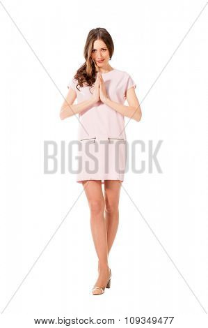 Young slim pretty woman in pink dress praying isolated on white background