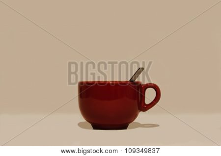 Large glossy red round cup with a handle and a spoon