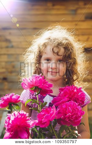 Curly Baby With Flowers In Her Hand. Toning Photo. Instagram Filter.