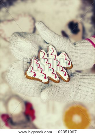 Child hands in gloves holding gingerbread cookies - Vintage Christmas background