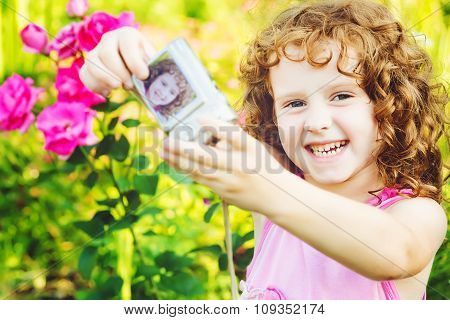 Laughing girl taking selfie with photo camera.