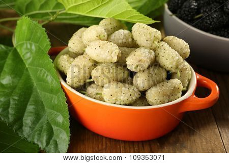 Ripe mulberries in bowls with green leaves on table close up