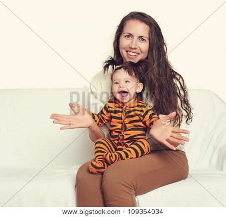 woman with child girl portrait sitting on sofa and playing