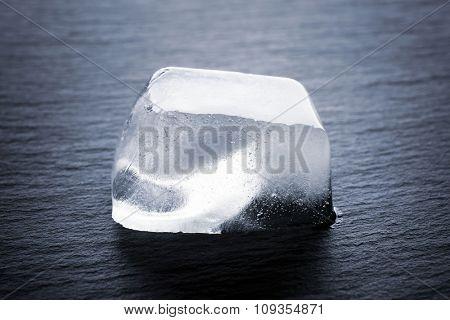 Matted ice cube on dark liquid background