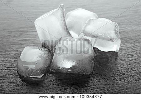 Matted ice cubes on dark liquid background