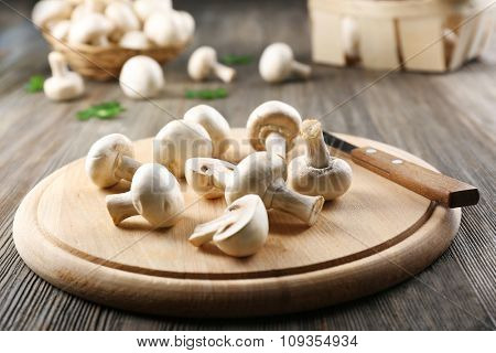 Champignon mushrooms and a knife on wooden background