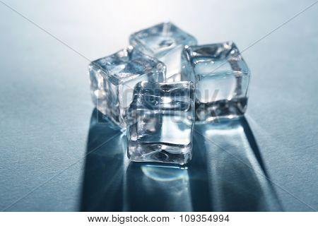 Shining ice cubes on grey-blue background