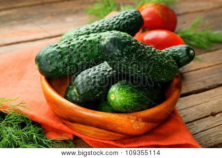 Fresh cucumbers with red cotton serviette and tomatoes on wooden table