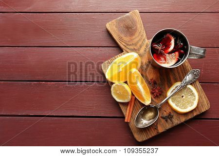 Mulled wine in a mug with citruses on wooden background