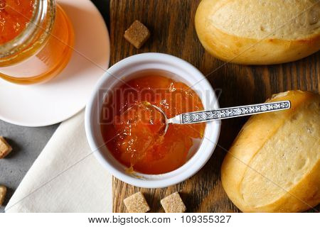 Tasty jam in the jar and bowl, crackers and fresh buns close-up