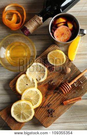 Delicious mulled wine in a mug with citruses on decorated wooden background, close up