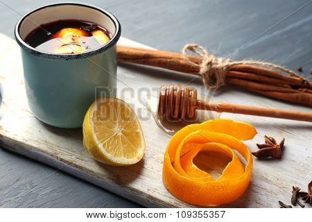 Mulled wine in a mug with citruses on board against grey wooden background, close up