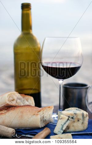 Beautiful romantic composition of red wine, bread and nuts on sandy beach, close up
