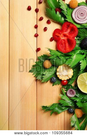 Cute colourful bouquet of sliced vegetables on wooden background, close up