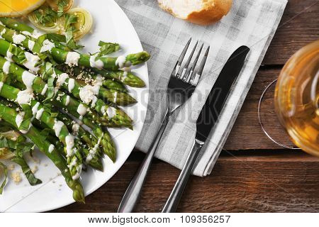 Served wooden table with asparagus dish and wine, close up