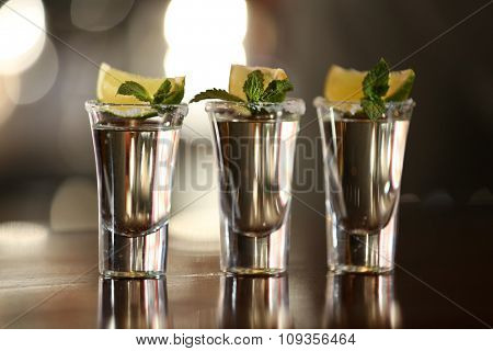 Shot glasses with tequila on bar counter