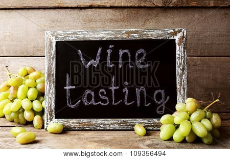 old square chalk scripted frame with grape on wooden background