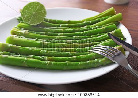 Fresh asparagus with lime on white plate against wooden background, close up