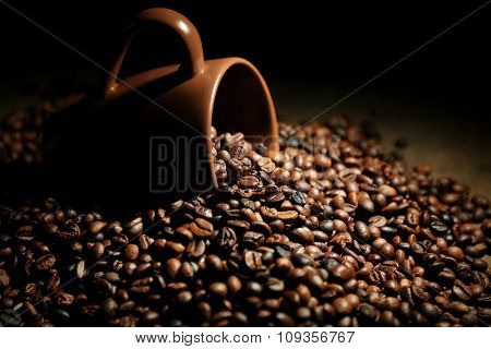 A brown cup and aromatic coffee beans scattered on wooden background