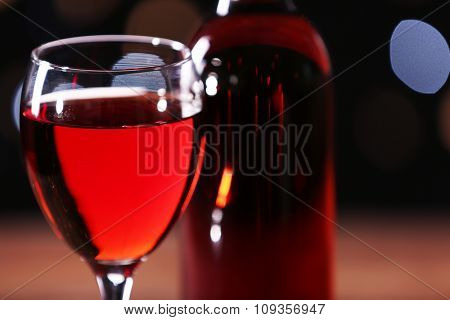 Wine glass with bottle on wooden table against black bukhe background, close up