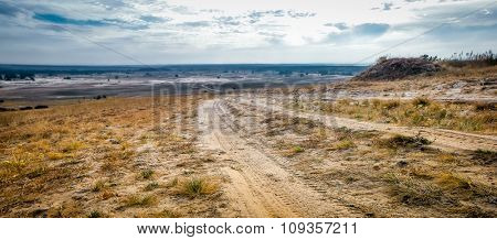 scenic landscape of rolled road in a sandy field
