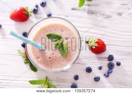 Fresh strawberry yogurt with berries around on light wooden background