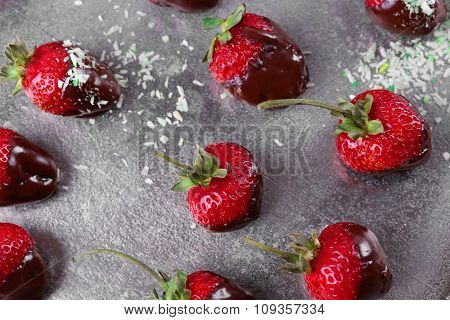 Delicious strawberries in chocolate on metallic background