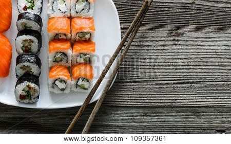 Japanese sushi on white plate with chopsticks on wooden background
