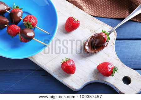Delicious strawberries in chocolate on kitchen table
