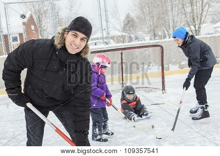 A family playing at the skating rink in winter.