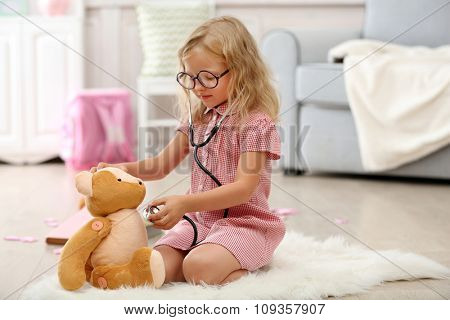 Little girl playing with toy bear in the room
