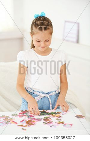 Cute little girl playing with puzzles on home interior background