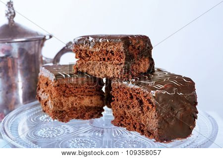 Served table with a teapot and chocolate cakes on white background
