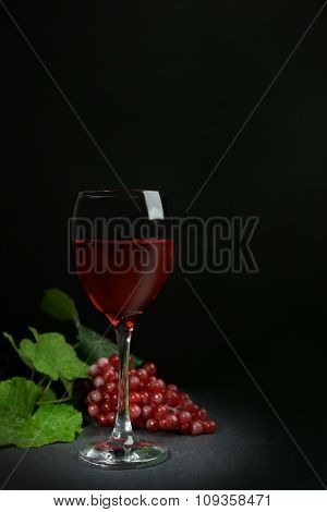 A glass of wine and red grapes, on grey-black background