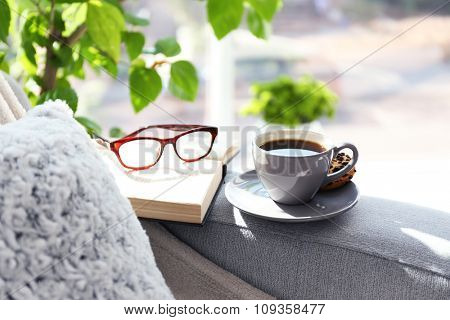 Cup of coffee with book on sofa in room