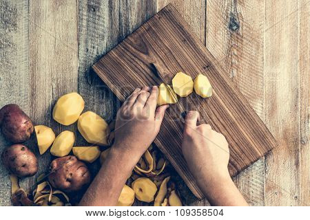 hands cutting potato on wooden board