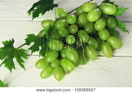 Bunch of white grape on white wooden background