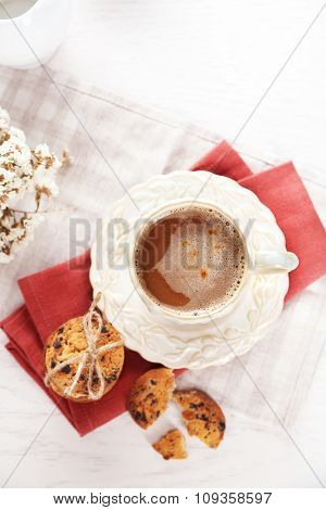 Cup of coffee and pile of tasty cookies with chocolate crumbs on white wooden table