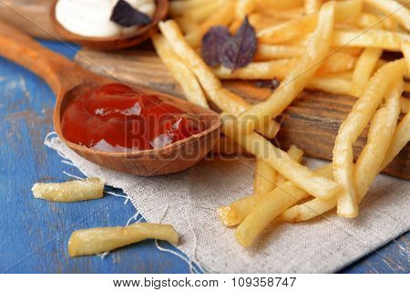 French fried potatoes with sauce on cutting board