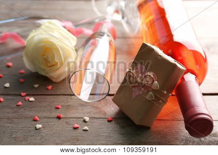 A bottle of wine, a glass, a white rose and a gift in the box, on wooden background